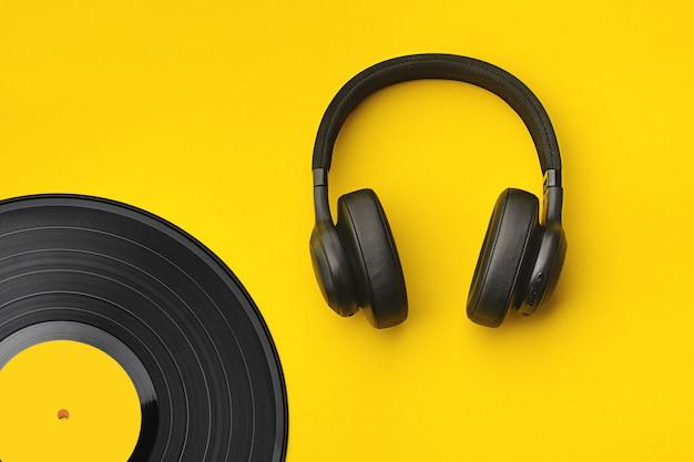 Черные беспроводные наушники с виниловой пластинкой. музыкальная концепция.