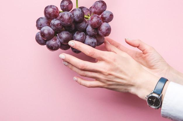 女性の手がピンクの背景のブドウを選ぶ