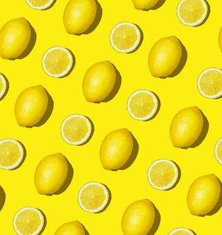 新鮮なレモンと色付きの背景にレモンスライスのカラフルなフルーツパターン。レモンスライストップビュー、フラットレイアウト