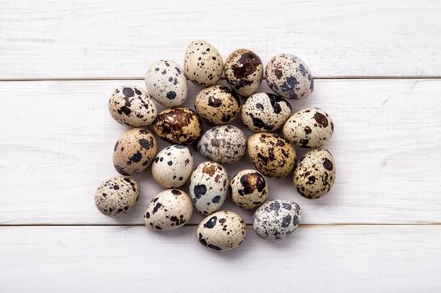 ボードから白い背景にウズラの卵。ウズラの卵の山
