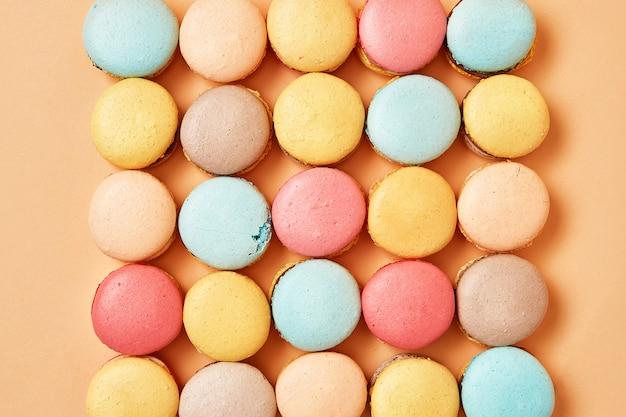 黄色の桃の背景にベージュ、茶色のフレンチクッキーマカロン