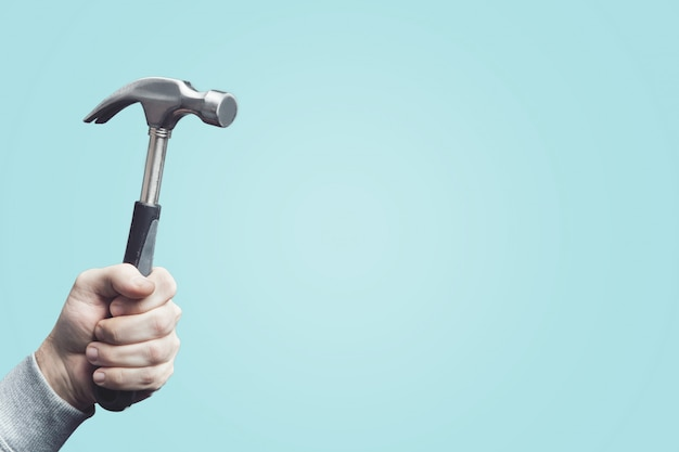 Человек, держащий старинный молоток, инструмент в руке.