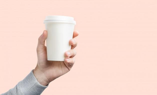 手にコーヒーの紙コップ。分離された手でコーヒーのホワイトペーパーカップ