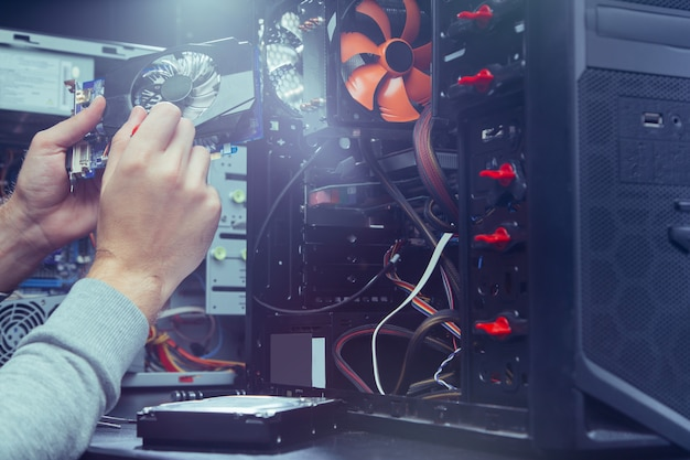 コンピューターを修理する技術者、マザーボード上のコンポーネントを交換するプロセス。