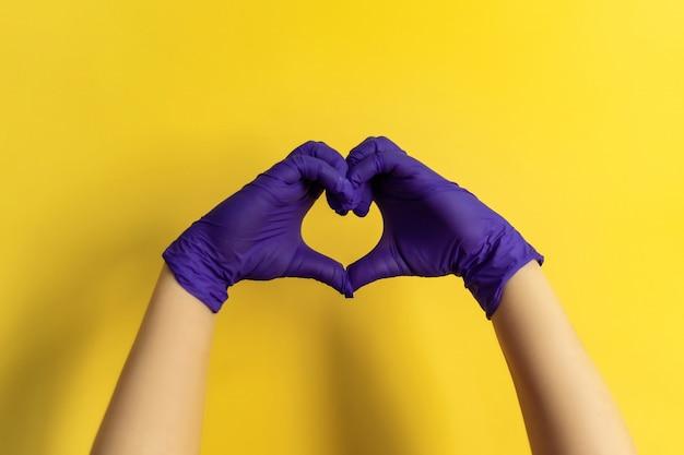 手でハートのサインを示す医療従業員、慈善寄付を求める