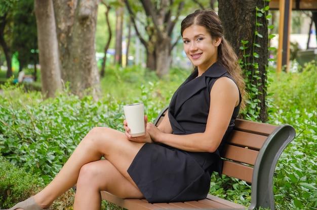 一杯のコーヒーで公園のベンチに座っている女性実業家