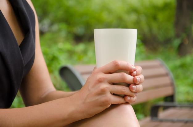 ベージュのカップを保持している女性の手の側面図