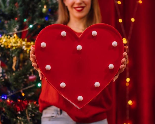 Женщина держит большое красное сердце. праздничный декор