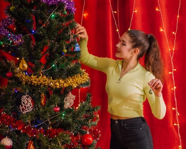 笑顔の女の子がクリスマスツリーを飾る