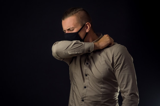 Локоть кашель. человек в защитной маске над черной стеной