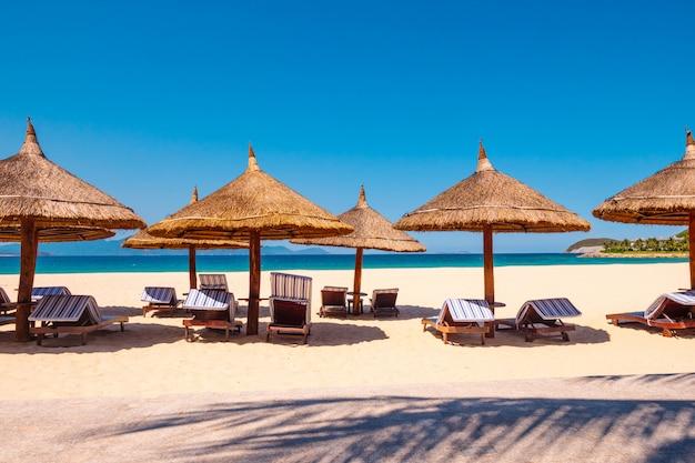 Роскошный курорт. зонтик с шезлонгами на пляже возле океана.