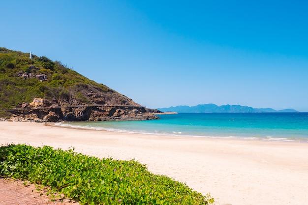 Пляж с океаном возле скалистого острова