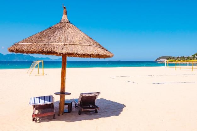 Роскошный пляж рядом с отелем. стулья и зонтик на пляже
