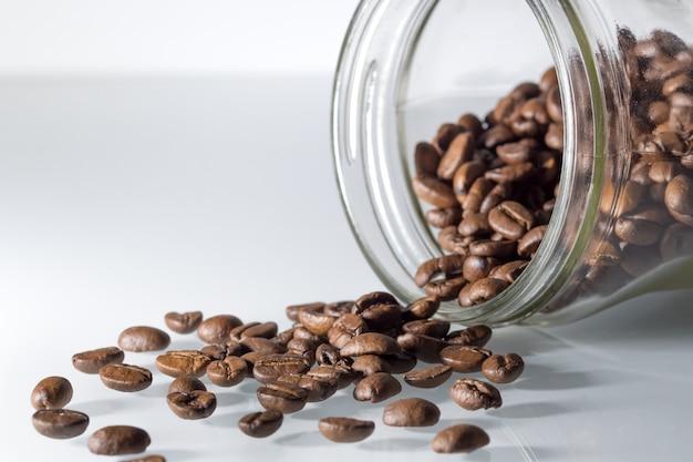 Кофейные зерна на белом столе с прозрачной банкой
