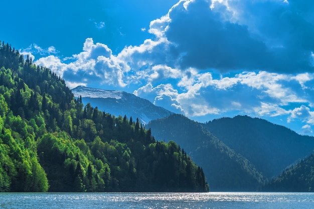 Красивое озеро рица в горах кавказа. зеленые холмы горы, голубое небо с облаками. весенний пейзаж.