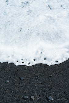 白い泡のある海の波が小石のある黒い砂のビーチを転がります。テネリフェ島の火山砂浜。