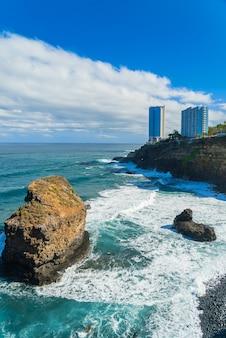 プンタブラバ、プエルトデラクルーズ、テネリフェ島、カナリア諸島、スペインの岩の上の海の海岸とホテルの建物を見る