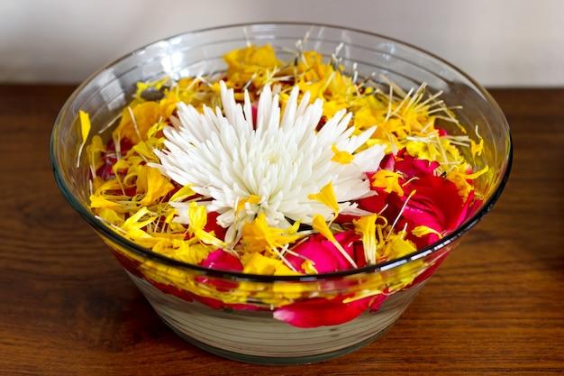 水と花瓶に花びらを持つ菊