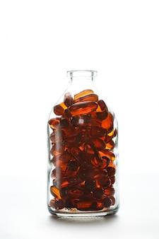 白い背景の上のゼラチンカプセルの瓶