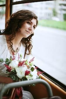 窓の近くに座って花を持つ若い女性