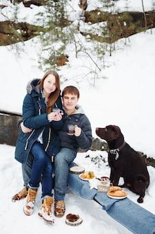 Пара пьет горячий напиток на открытом воздухе