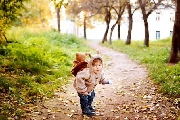 黄金色の秋に公園で楽しんで暖かい服でかわいい幼児