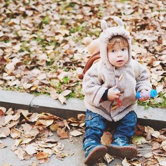 黄金の葉に座っている動物の耳フード付きかわいい幼児
