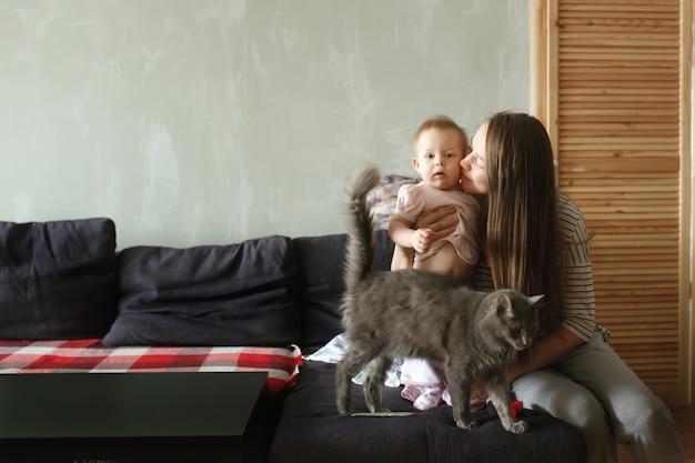 Молодая красивая мама сидит на диване у себя дома, обнимая и целуя ее сладкий ребенок