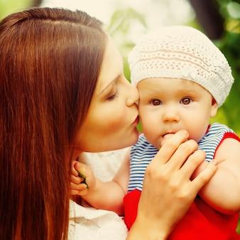 Милый малыш, сидящий на руках мамы