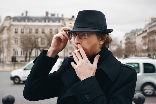 Привлекательный бородатый мужчина курит на улице