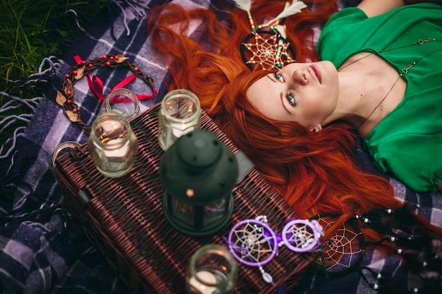 草で横になっている美しい赤髪の女性