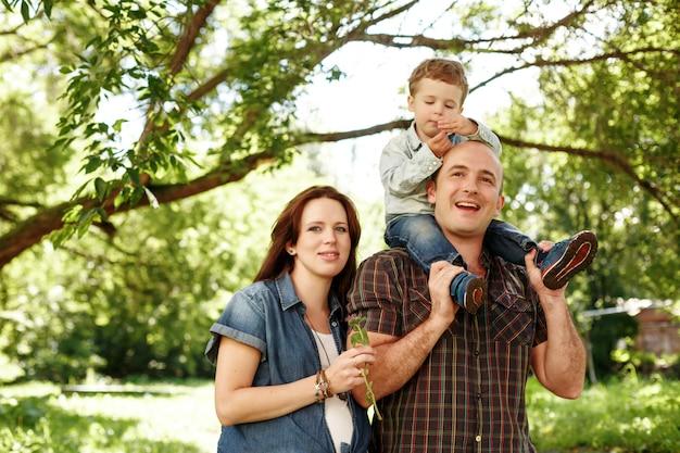 夏の屋外を歩いて幸せな家族
