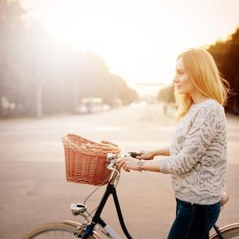 ビンテージ自転車の若いブロンドの女性