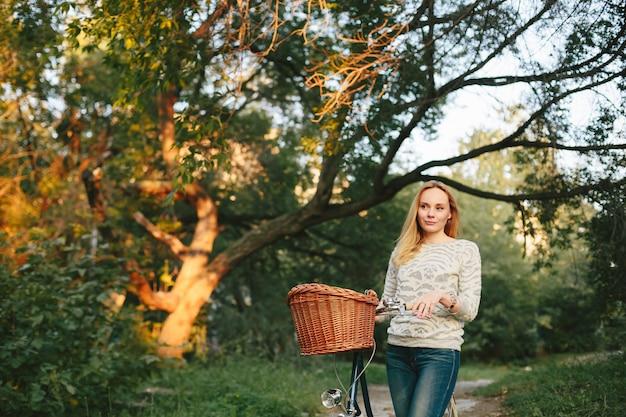Задумчивая женщина на винтажном велосипеде