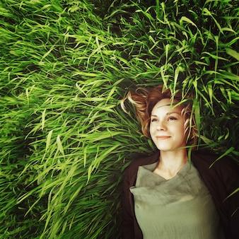 美しい若い女性は草の中に横たわっています。