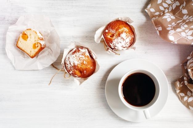 一杯のコーヒーと甘い新鮮な焼きたてのマフィン