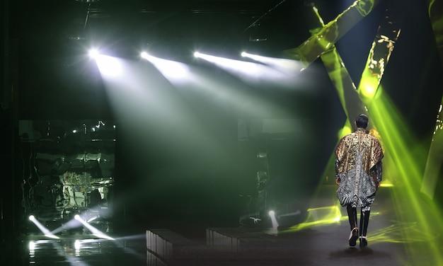 床に反射した鏡の滑走路ファッションショーのキャットウォークに戻って歩くモデル