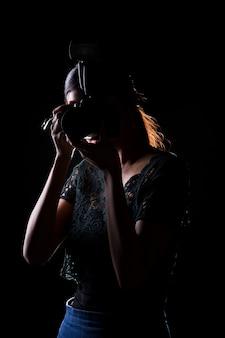 女性写真家は、外部の引火点、分離された黒の背景を持つカメラを保持します。