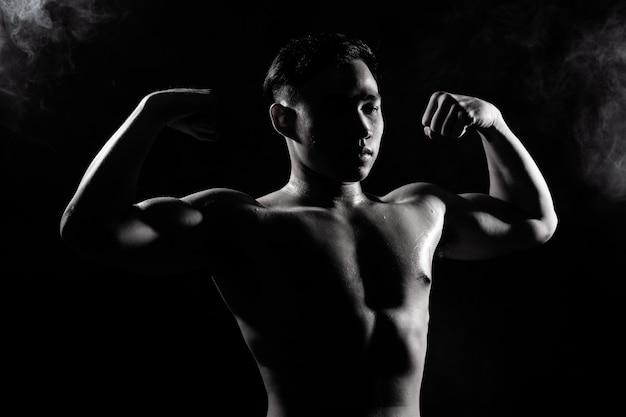 筋肉フィットネス男は暗い背景のシルエットで健康的なライフスタイルを行使します。