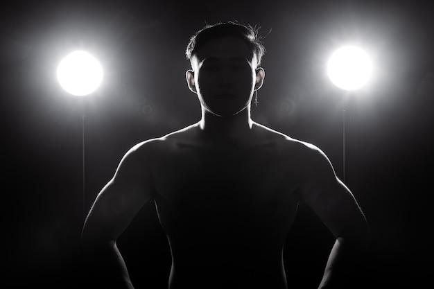筋肉フィットネス男は暗い背景シルエットバックライトで健康的なライフスタイルを行使します。