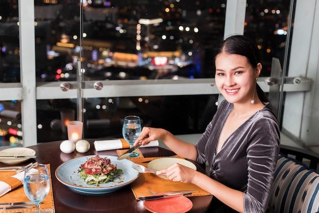 アジアの美しい女性は、高級屋上レストランで夕食をとります。