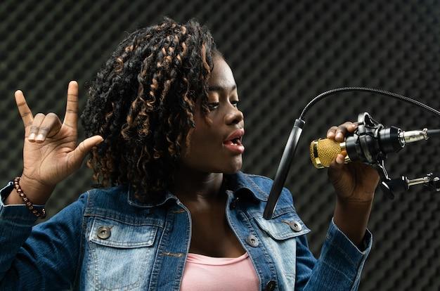 アフリカのティーンエイジャーの女性アフロ髪歌を歌う