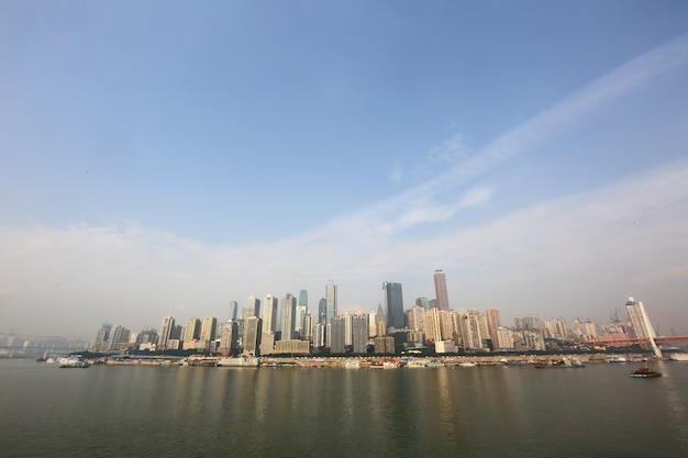 川の土手に空の都市スクレーパーと昼間の水と空の雲を反映