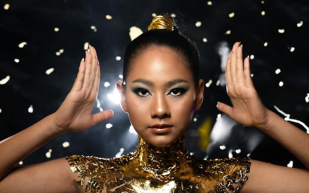 Женщину украшают золотой фольгой или сусальным золотом