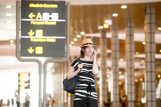 Женщина с шляпу говорить на своем телефоне