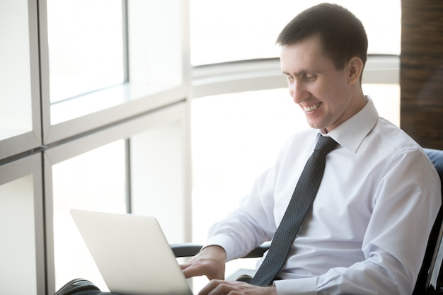 Улыбаясь человек, набрав на ноутбуке