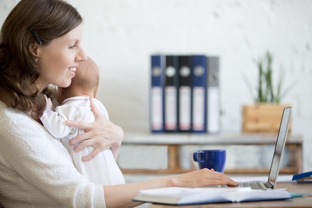 自分のラップトップを見て赤ちゃんを持つ女性