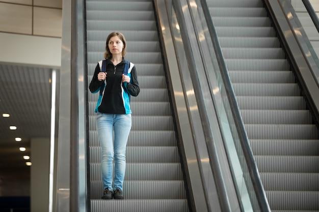 Женщина, спускаясь эскалатора