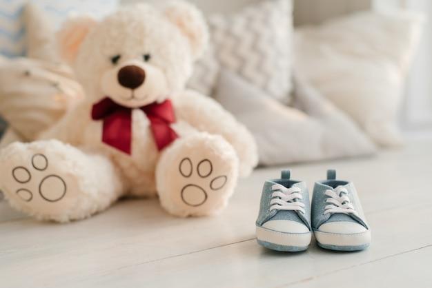 Маленькие детские синие кроссовки и мягкие игрушки. концепция ожидания новорожденного.