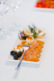 Лосось с закусками на белой тарелке и вилкой на столе